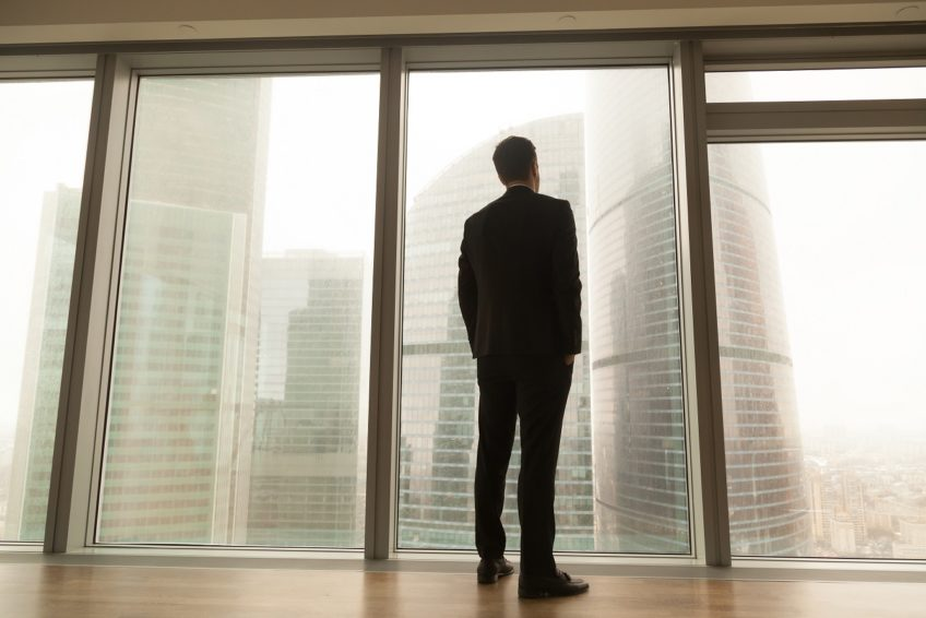 Businessman standing near full-length window looking at city, ba