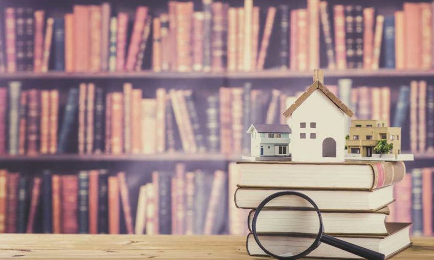 houses sat on top of books with a magnifying glass in the foreground, bookshelves are in the background