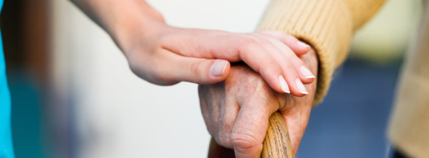 carer holding an elderly person's hand as they grip onto a walking stick
