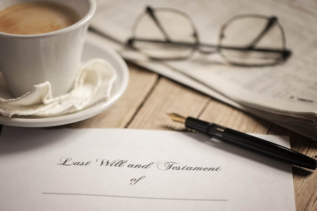 Last will and testament document with pen, cup of tea and glasses on table