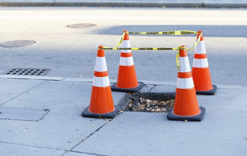 pothole on the sidewalk fenced. traffic cones and cordon type around the hole on the pavement