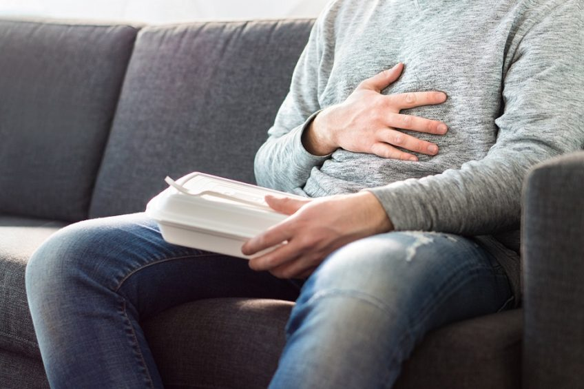 Stomach pain, food poisoning or digestion problem after fast junk food. Man ate too much and is holding belly with hand. Indigestion, heart burn or unhealthy diet.