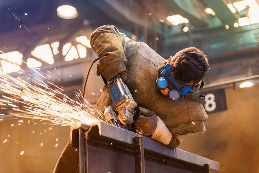 Engineer cutting metal with sparks flying