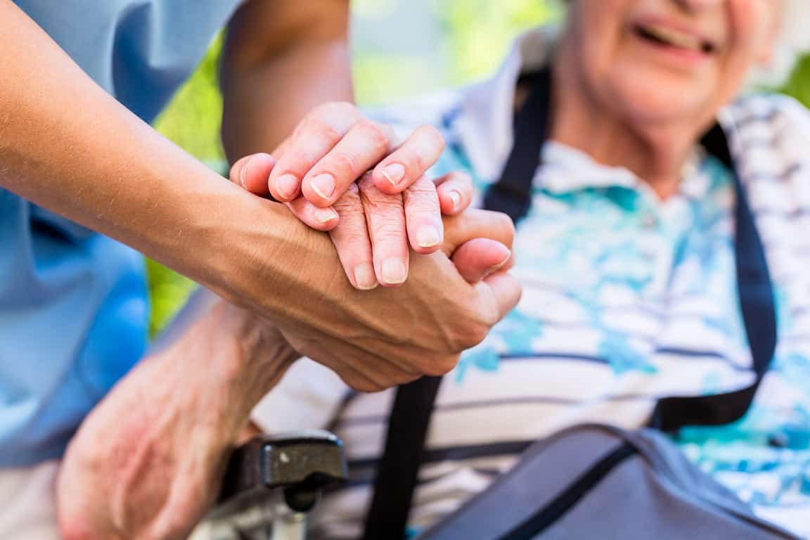 Nurse consoling senior woman holding her hand