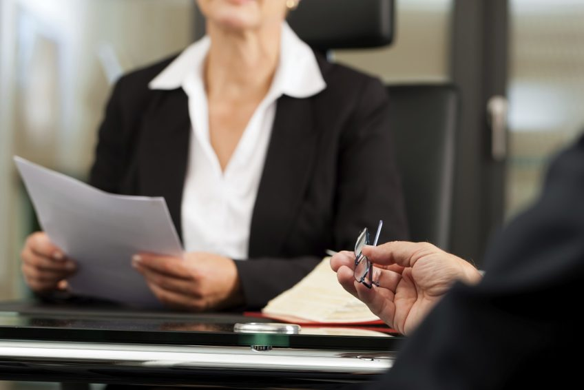 image of man holding glasses while speaking to a female lawyer who is holding documentation