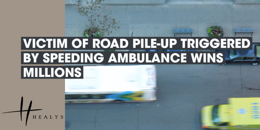 ambulance driving down a road past a bus and car