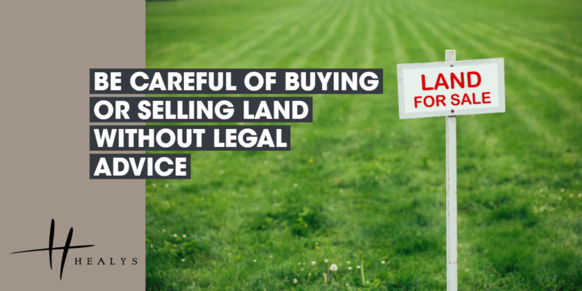 field with a sign which reads land for sale