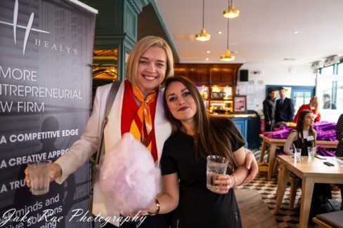 image of two female event attendees standing together and smiling while holding drinks and candy floss