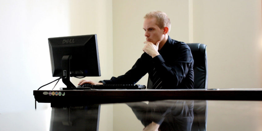 Male business manager wearing suit sat at desk reading on his computer