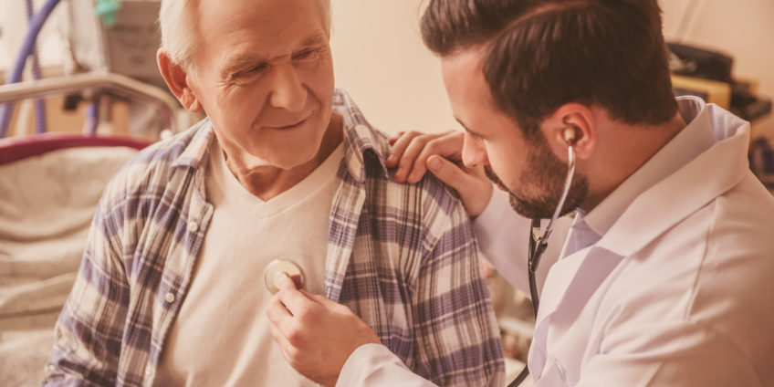 Doctor is listening to the heartbeat of an old man using a stethoscope
