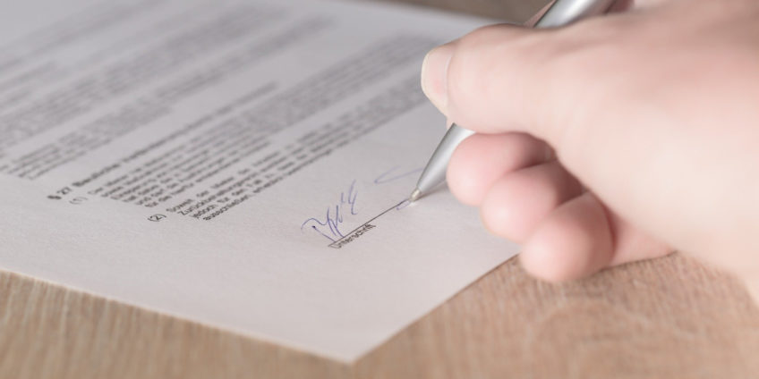 Close up of hand signing a contract