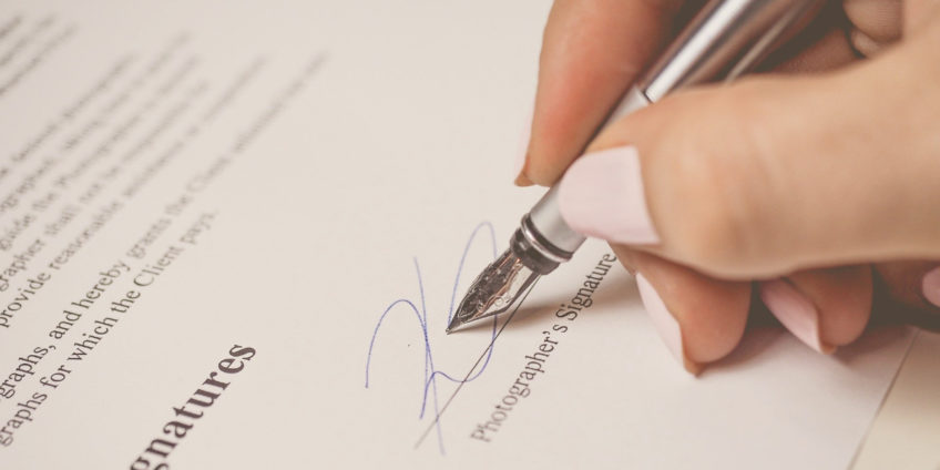 Womans hand signing contract