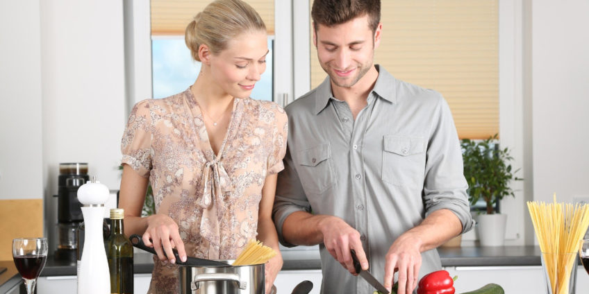 Couple cutting vegetables to prepare for cooking