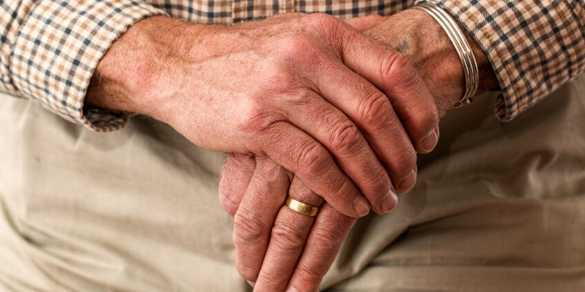 elderly man holding his hands together