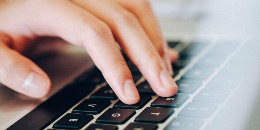 close up of hand typing on laptop keyboard