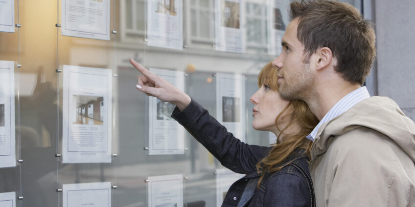 Couple Looking At Display At Real Estate Office