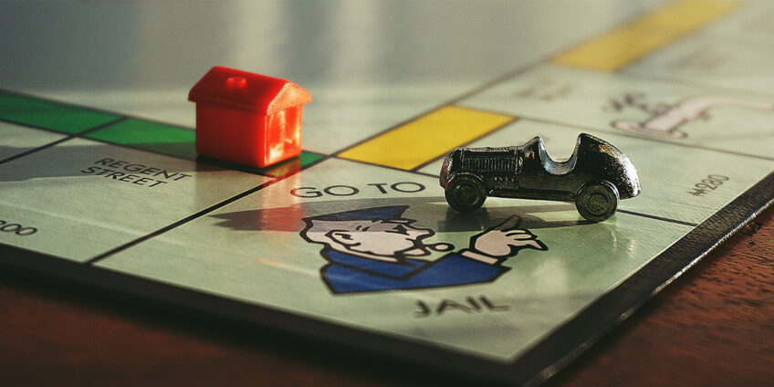 photo of a monopoly board, focused on the go to jail square, on which the car figure sits