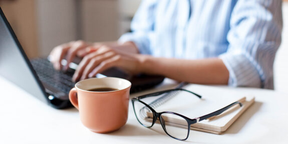 woman working at laptop, with a mug, glasses and notepad resting on the desk beside it