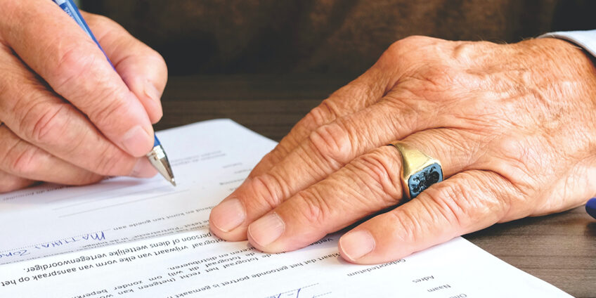 close up of elderly man's hand signing documents